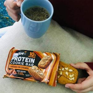 Pessoa comendo Cookie Proteico Amêndoas com especiarias com café