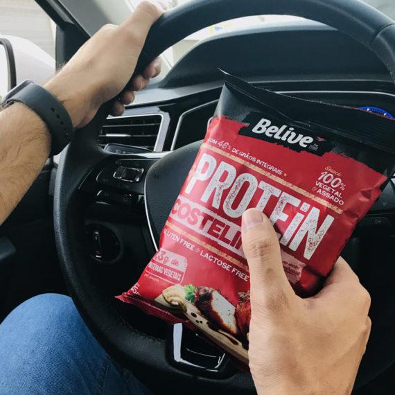 pessoa com snack proteico no carro