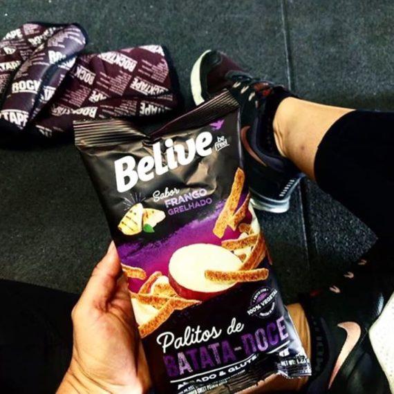 mulher segurando snacks proteicos sabor frango grelhado na academia