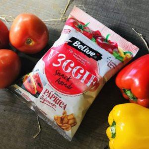 snacks saudaveis sabor paprica defumada na mesa com tomates e pimentas
