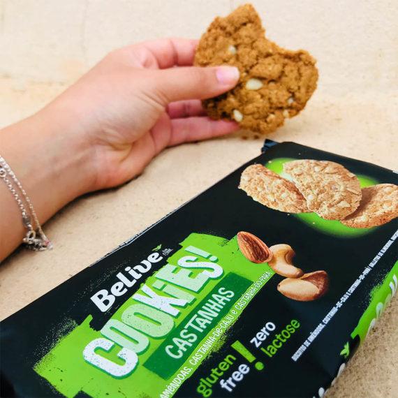 Mão segurando o cookie sem glúten de castanhas da Belive