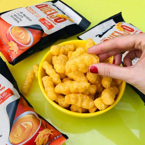 Snack Fit de Milho em bowl amarelo e mesa amarela, 3 embalagens sabor Queijo Nacho da Belive